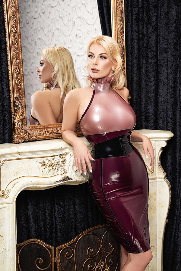 Prachtige blonde Mistress Vernice in latex voor spiegel